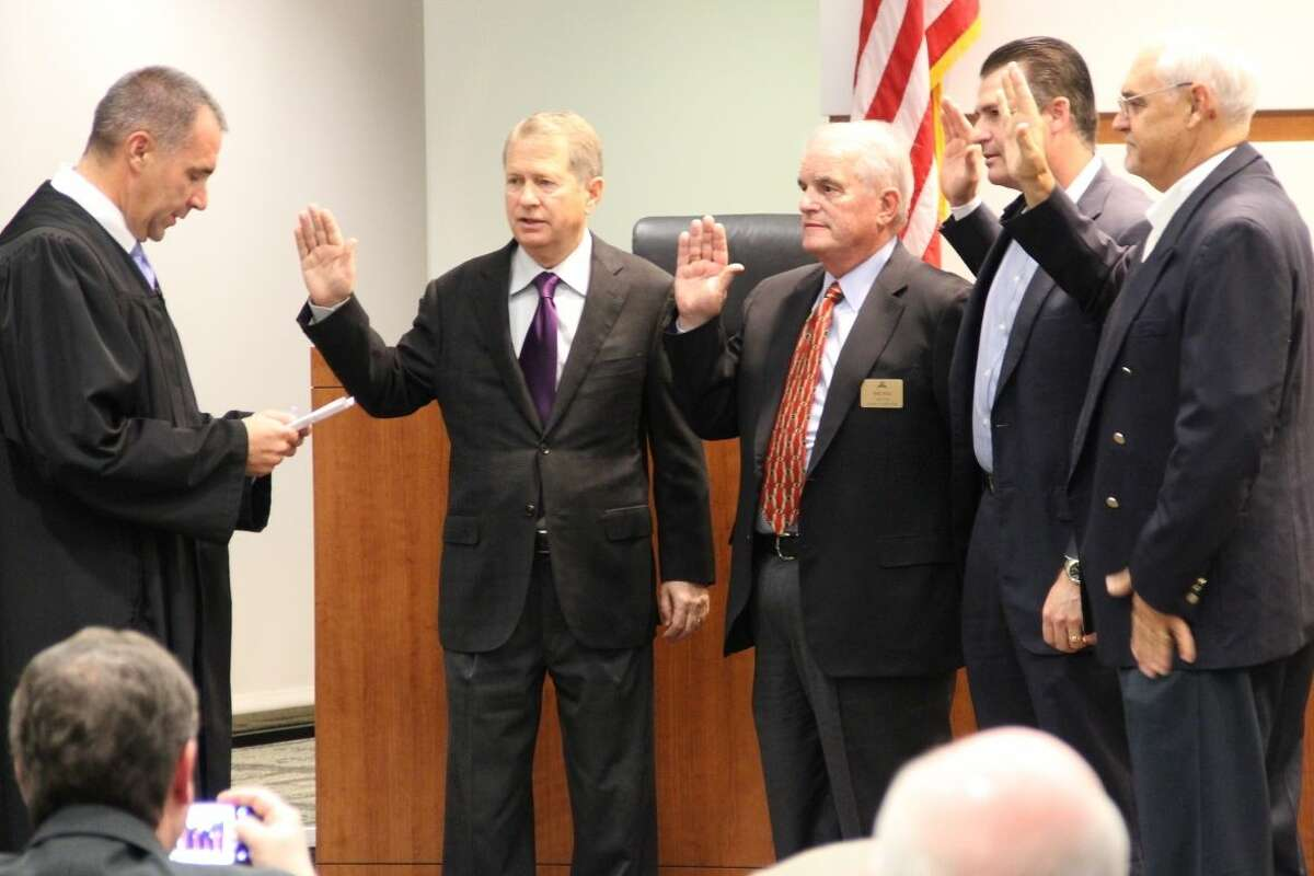 435th state District Judge Michael Seiler, left, administered the oaths of office to all four re-elected members of The Woodlands Township Board of Directors at the township regular meeting, Wedneday, Nov. 19 - left to right, Ed Robb, Mike Bass, Gordy Bunch, Jeff Long.