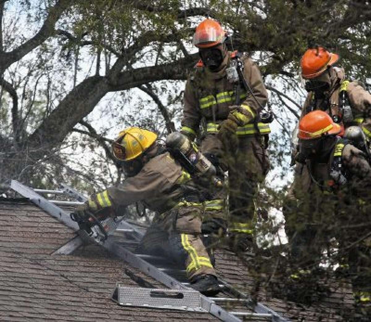 League City Firefighters work on the roof at a house fire on Moody Avenue.