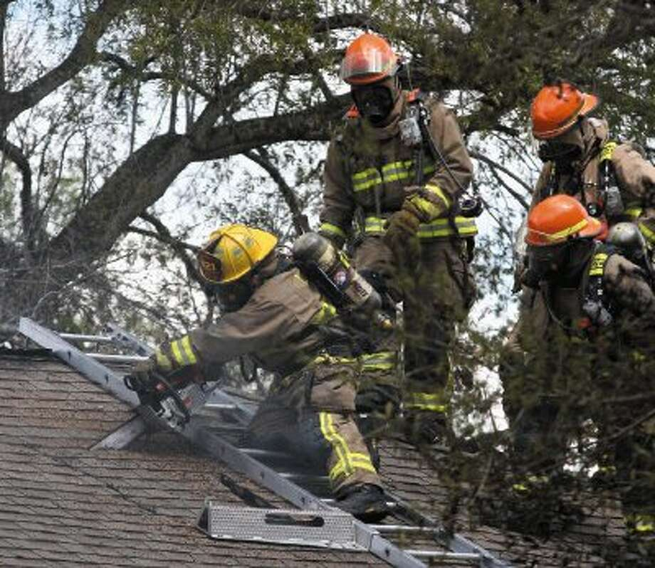 League City Firefighters work on the roof at a house fire on Moody Avenue. Photo: Kar B Hlava