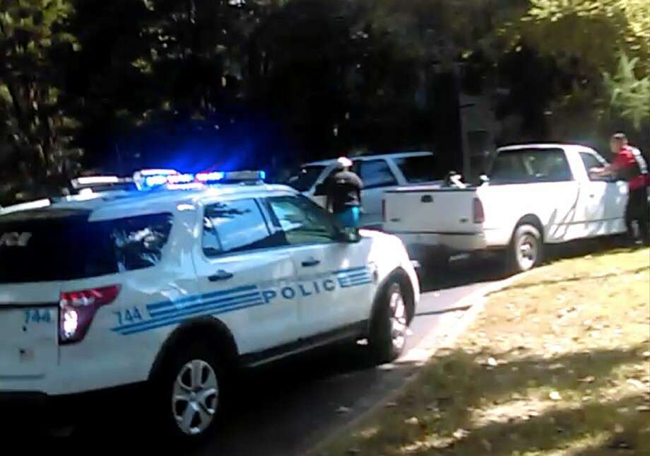In this image taken from video recorded by Rakeyia Scott on Tuesday, her husband, Keith Lamont Scott, center, stands amid Charlotte police cars and other vehicles moments before he is shot by a police officer in Charlotte, N.C.