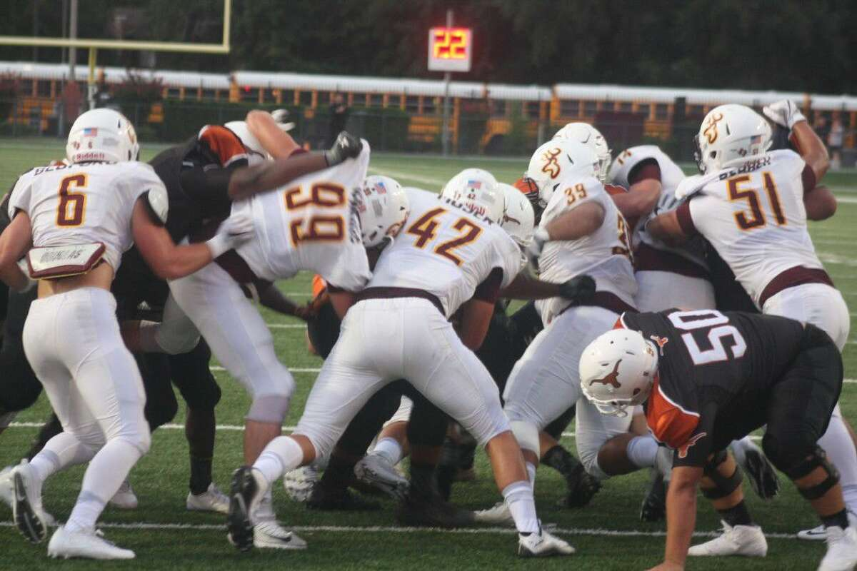 Race Moser (42), Brody Jenkins (99) and the rest of the Deer Park defense stops a Dobie ballcarrier at the goal line in the first quarter.