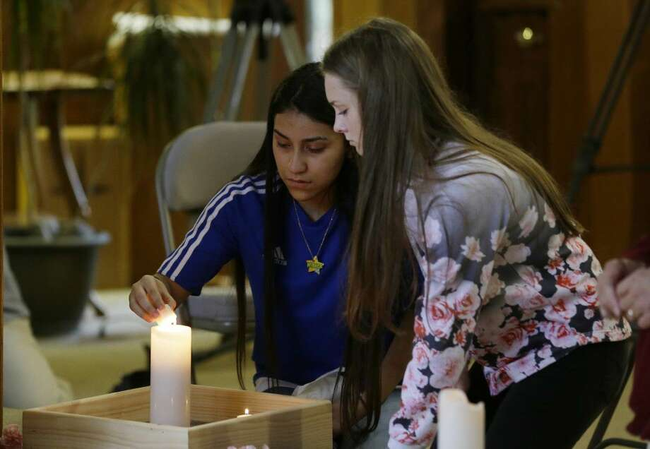 Rachel Marsh, 15, right, and Selena Orozco, 15, left, light candles as they attend a prayer service, Saturday at the Central United Methodist Church in Sedro-Woolley, Wash.
