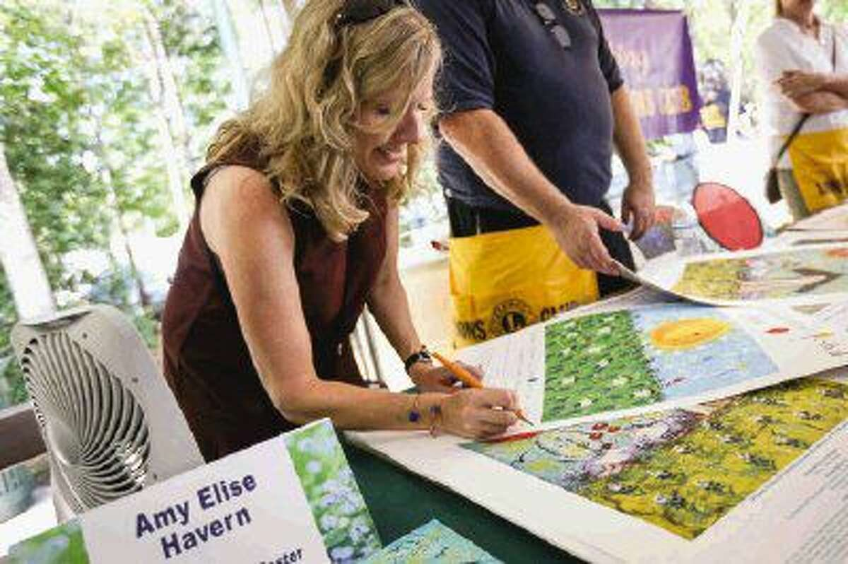 Amy Elise Havern signs a poster with her artwork on it at The Woodlands Lions Club booth during The Woodlands Wildflower Festival Saturday at Town Green Park.