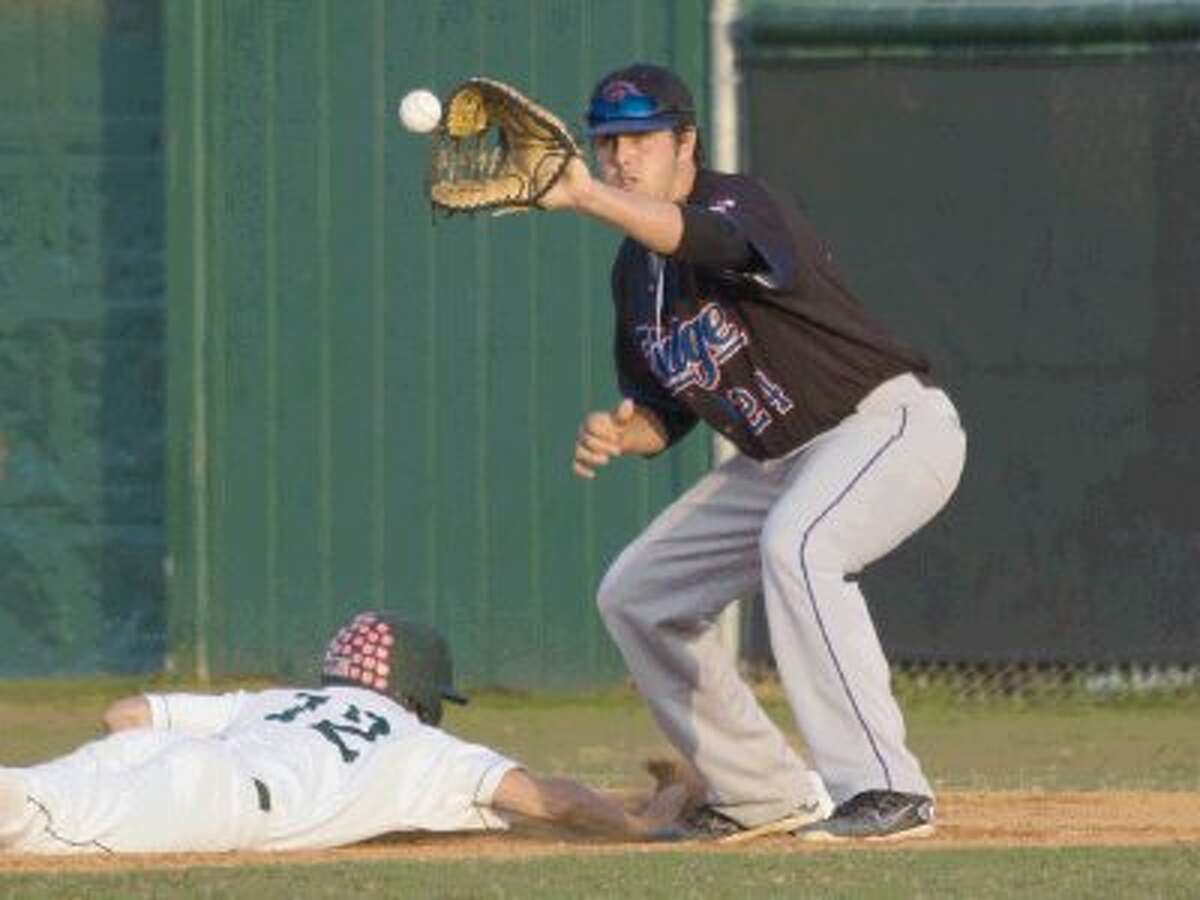 The Woodlands' Evan Brain slides back to first base as Oak Ridge's Kym Plympton catches the ball during a high school baseball game at Scotland Yard at McCullough Junior High School in The Woodlands Friday. Oak Ridge won 5-4. To view or purchase this photo and others like it, visit HCNpics.com.