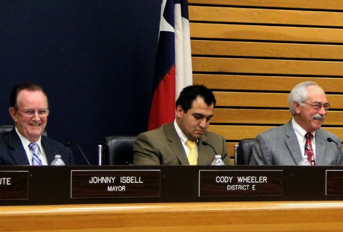 Mayor Johnny Isbell (left) and Councilmember Phil Cayten (right) laugh at a comment made by another member. In contrast, the comments didn't draw as much as a smile from Councilmember Cody Wheeler (center), who has strongly opposed changes to the council meetings that would limit comments from citizens and members.
