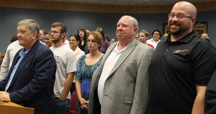 Members of New Harvest Christian Fellowship stand up behind Pastor Keith Anderson in support of a zone change.