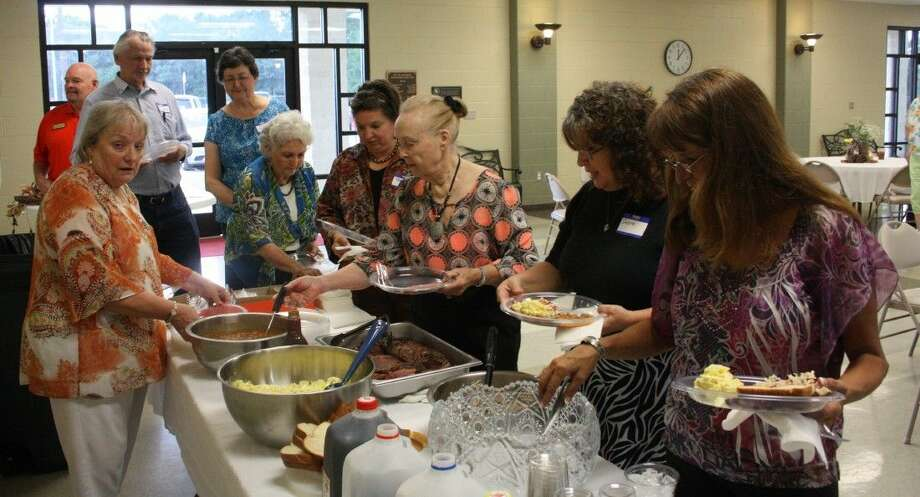 Chamber member Yvonne Ryba (left) serves brisket, potato salad and baked beans to those attending the Shepherd Chamber Luncheon's 60th anniversary. Photo: Staff Photo By Jacob McAdams