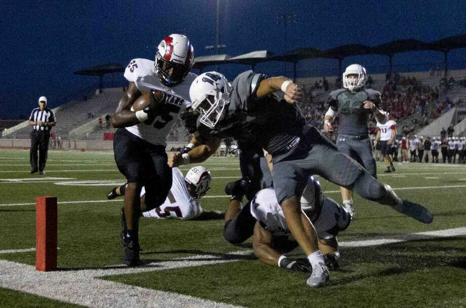 Porter running back Bradley Moore (25) runs for a 4-yard touchdown as Kingwood Park linebacker Sam Johansen (14) defends the Spartans' 31-0 win last week. Photo: Jason Fochtman