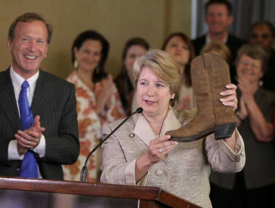 "Wendy Spencer, CEO of the Corporation for National and Community Service, uses a cowboy boot to illustrate the citywide effort to ""Stamp out Illiteracy"" while Barbara Bush Houston Literacy Foundation Chairman Neil Bush applauds."