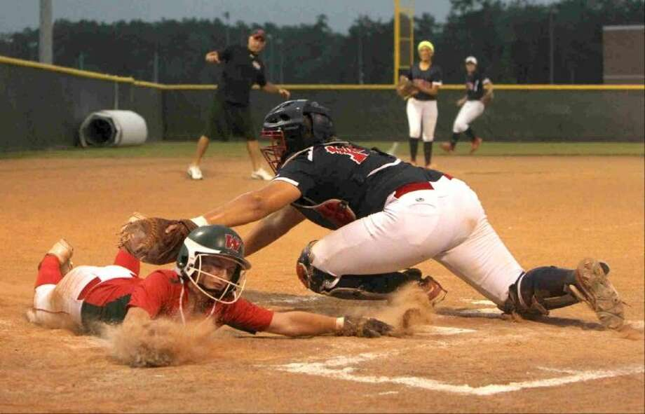 The Woodlands' Aubrey Leach beats the tag at home plate from Atascocita's Miranda Grotenhuis during Game 1 of a regional quarterfinal series at Porter High School Friday. To view or purchase this photo and others like it, visit HCNpics.com.
