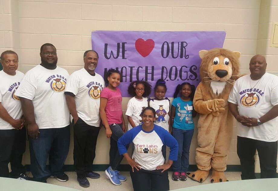 Deyna Herrera, parent liasion at Park Lakes Elementary in Humble ISD (front) poses with WATCH D.O.G.S. fathers, students and school mascot Lenny the Lion during the Dads and Kids Pizza Night launching the second year of Park Lakes' WATCH D.O.G.S. program Sept. 22 at Park Lakes Elementary in Humble.
