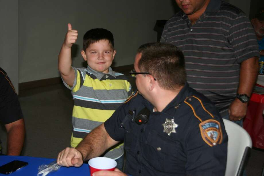 Brenden Zigmont gives Sean Mahan with the Harris County Sheriff's Office a thumbs up during the First Responders dinner Saturday, Sept. 24.