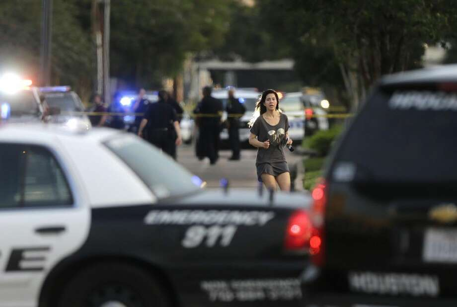 Jennifer Molleda runs down Wesleyan Street in Houston to find her husband, Alan Wakim, who had two bullets whiz by his face after going through his windshield on the way to work along Wesleyan at Law Street in a shooting that left multiple people injured and the alleged shooter dead, Monday morning.