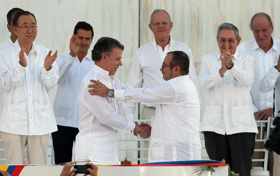 Colombia's President Juan Manuel Santos, front left, and the top commander of the Revolutionary Armed Forces of Colombia (FARC) Rodrigo Londono, known by the alias Timochenko, shake hands after signing the peace agreement between Colombia's government and the FARC to end over 50 years of conflict in Cartagena, Colombia, Monday.