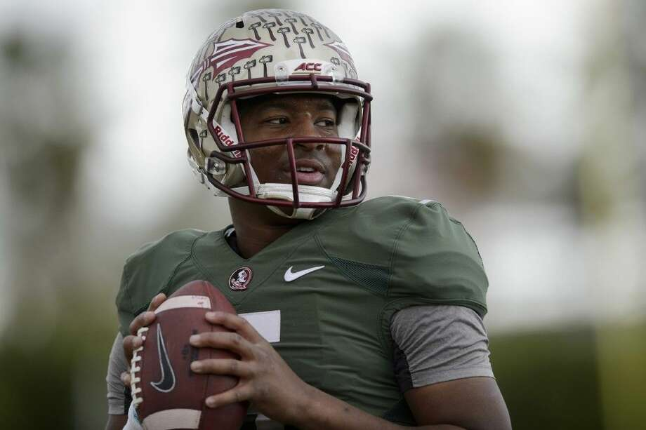 Florida State quarterback Jameis Winston throws the ball to warm up during an NCAA college football practice in Carson, Calif., on Tuesday.