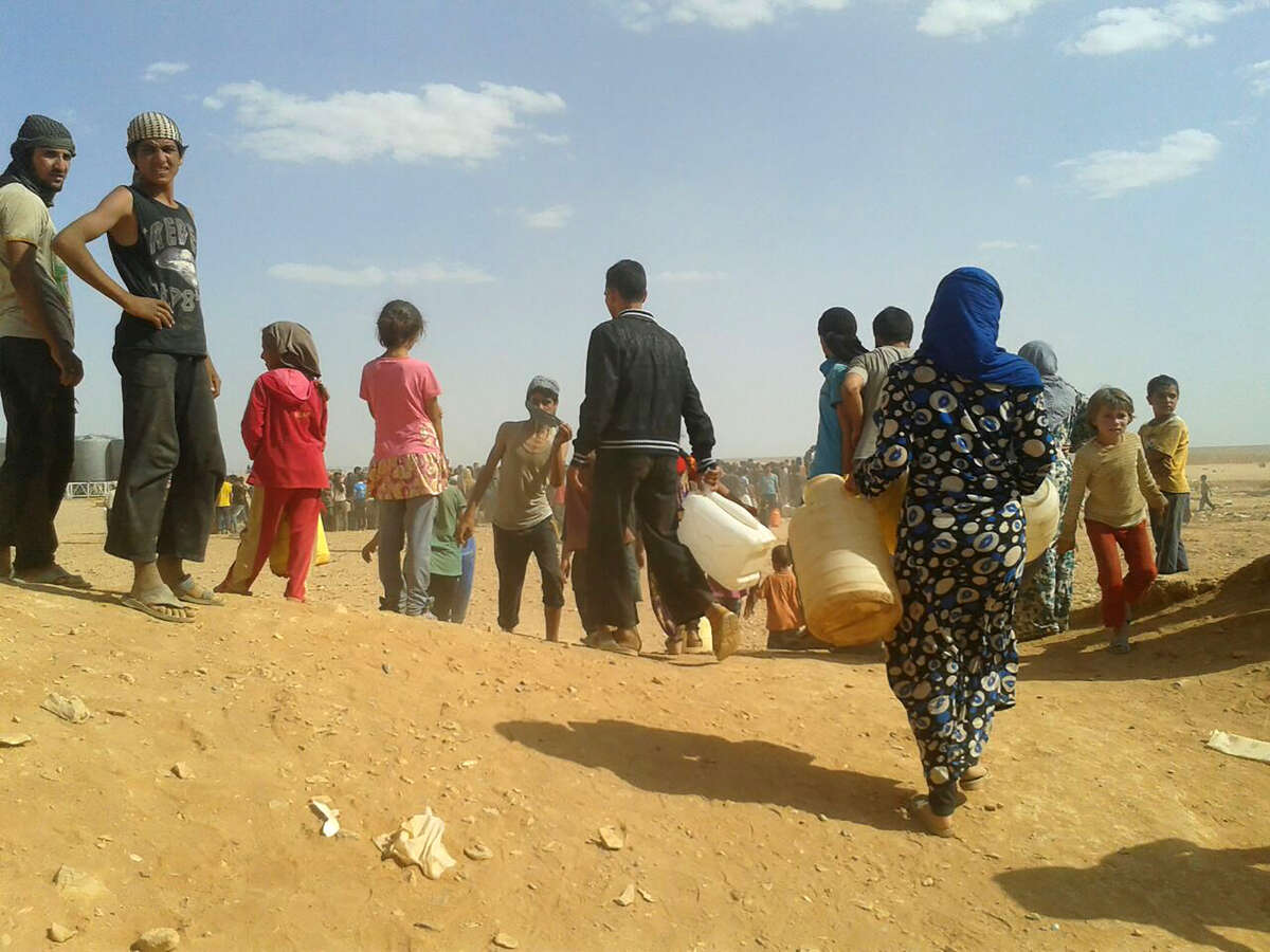 Syrian refugees gather for water at the Rukban refugee camp in Jordan's northeast border with Syria on June 23, 2016. (Associated Press file photo)