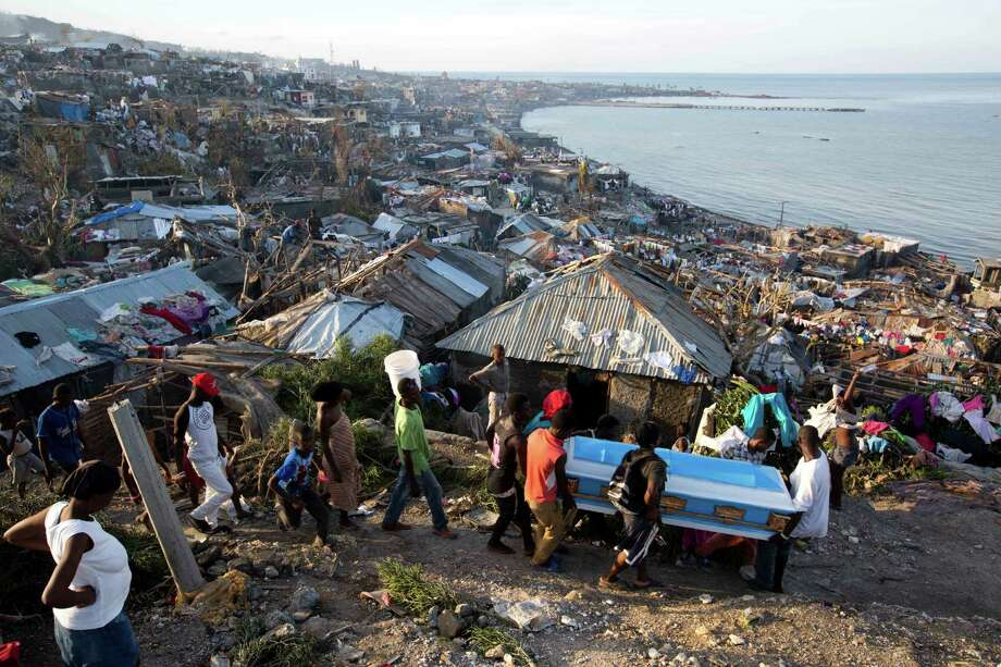 Residents carry a coffin containing the remains of a pregnant woman, a victim of Hurricane Matthew, in Jeremie, Haiti. Friday, Oct. 7, 2016. People across southwest Haiti were digging through the wreckage of their homes Friday, salvaging what they could of their meager possessions after Matthew killed hundreds of people in the impoverished country. Photo: Dieu Nalio Chery, AP / Copyright 2016 The Associated Press. All rights reserved.