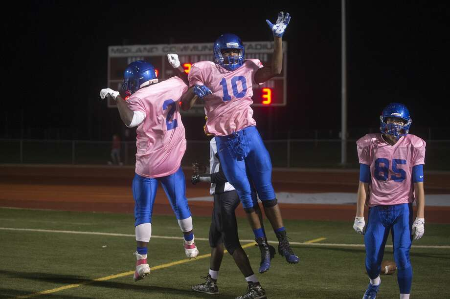 Midland High's Vondre Warren, left, and Vincent Walker celebrate Walker scoring a touchdown in the first half of Midland's game against Saginaw High. Photo: Brittney Lohmiller/Midland Daily News