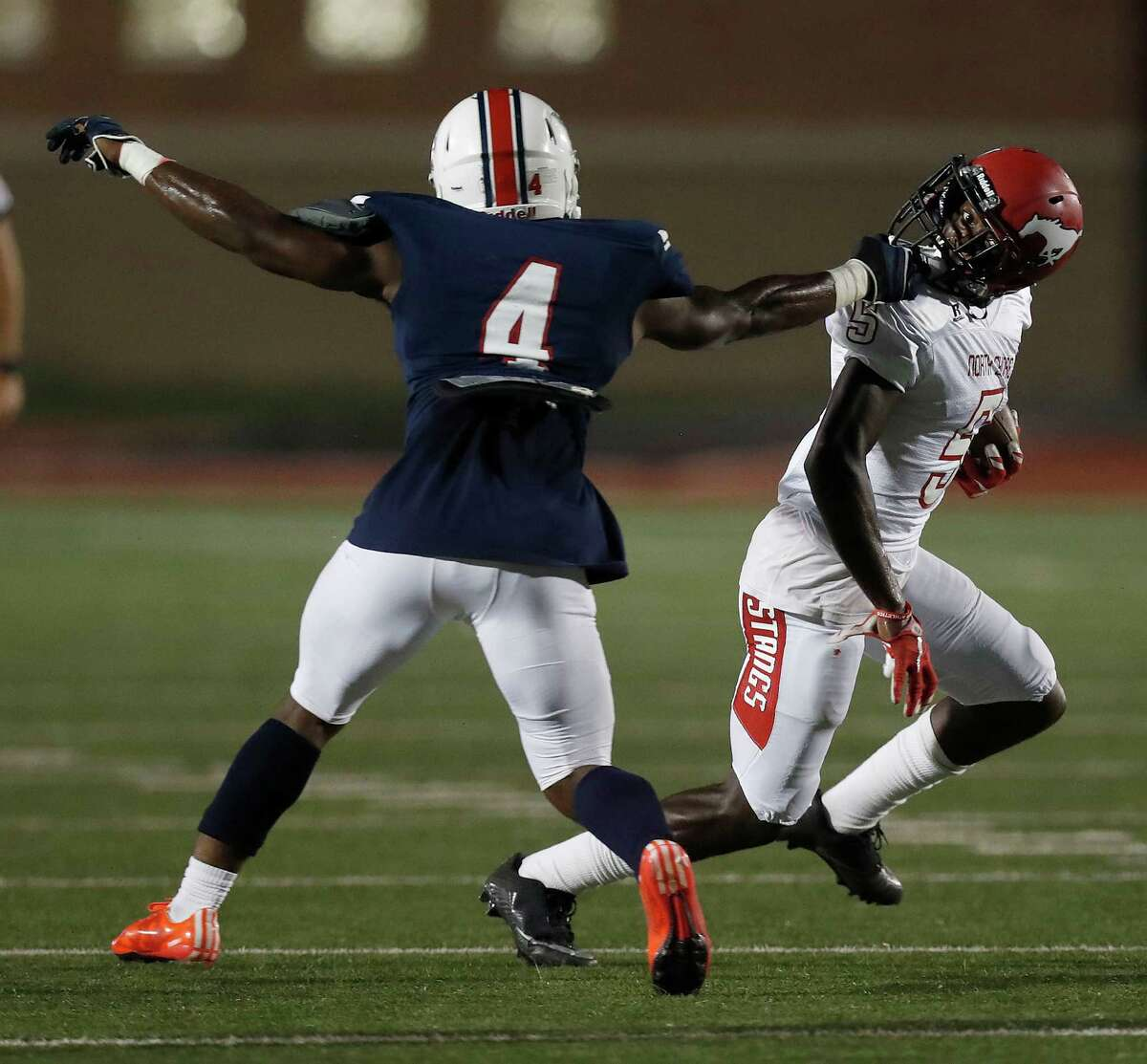 Atascocita's Tralan Hutchinson (4) grabs the facemark of North Shore wide receiver Patrick Davis (5) during the first half of a high school football game at Turner Stadium, Friday, Oct. 7, 2016 in Humble.