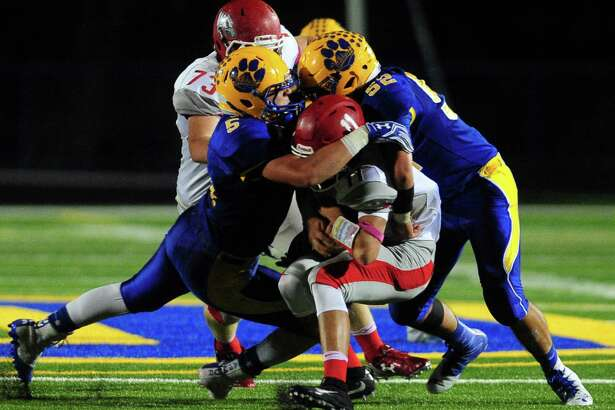 Seymour's Cade Klarides, left, and Adam Iacomacci sack Wolcott QB Mike Polzella during football action in Seymour, Conn. on Friday Oct. 7, 2016.