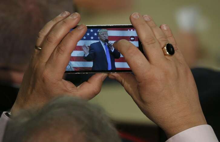 A man uses cell phone to take a photo of Republican presidential candidate Donald Trump as he speaks at a town hall event on October 6, 2016 in Sandown, New Hampshire. / AFP PHOTO / Mary SchwalmMARY SCHWALM/AFP/Getty Images