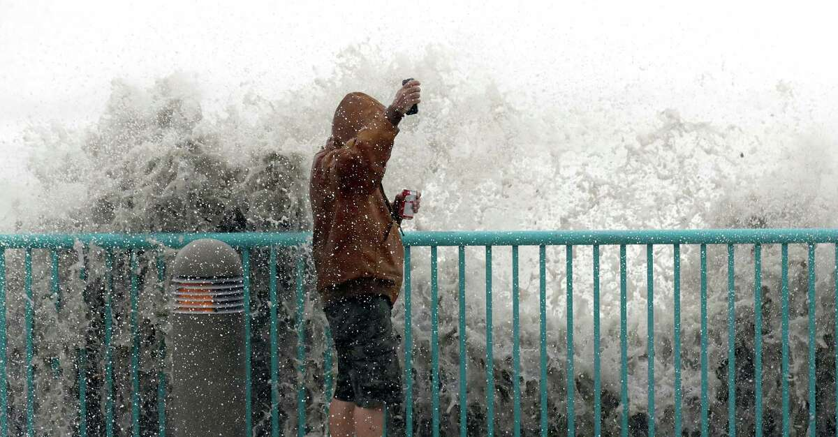 Brian Johns is hit by a wave Friday as he tries to video the effects of Hurricane Matthew in Daytona Beach, Fla.