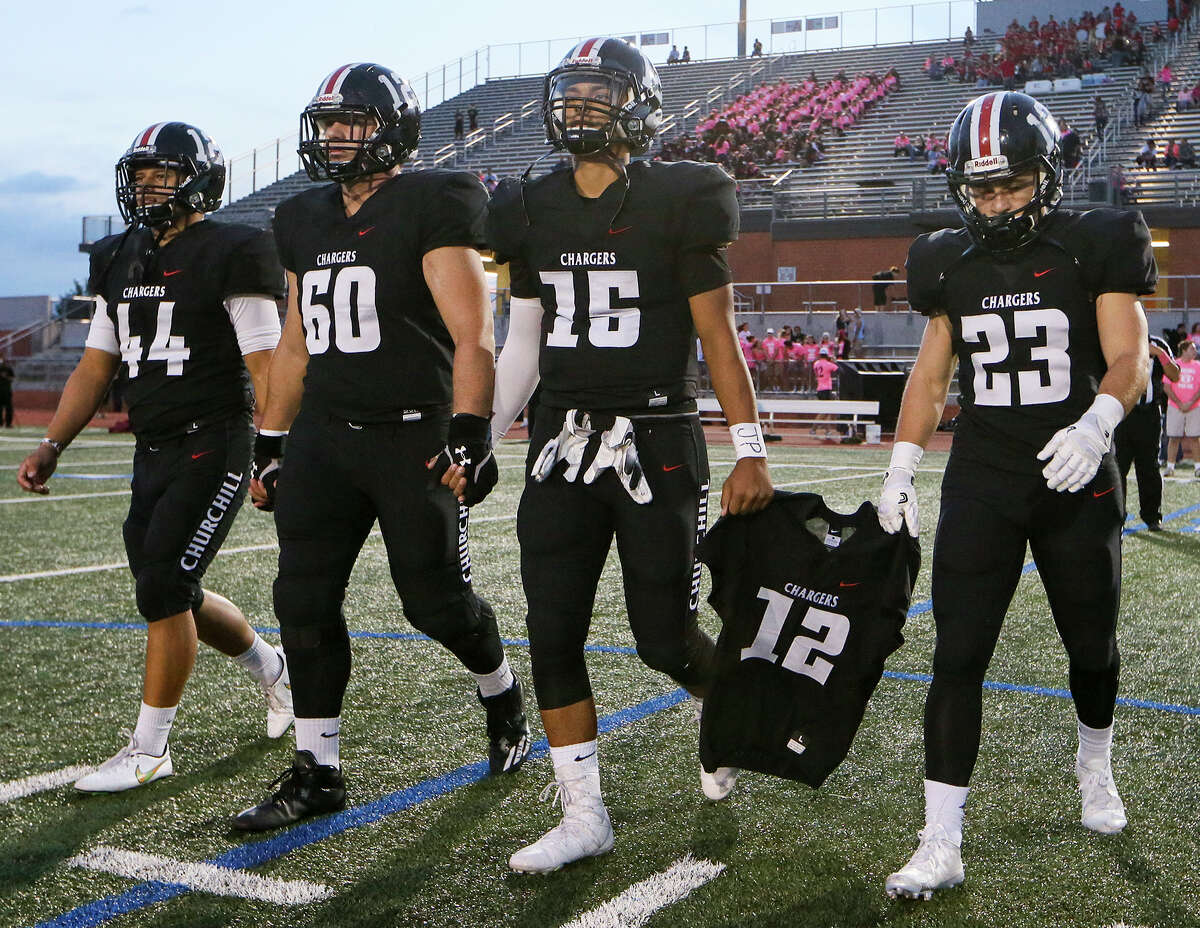 Churchill team captains Philip Mitschke (from left), Matthew Atkonis, Michael Sandoval and Thomas Sharrick carry the jersey of teammate Josh Pollard to the coin toss prior to the first half of their District 26-6A high school football game with Johnson at Heroes Stadium on Friday, Oct. 7, 2016. MARVIN PFEIFFER/ mpfeiffer@express-news.net