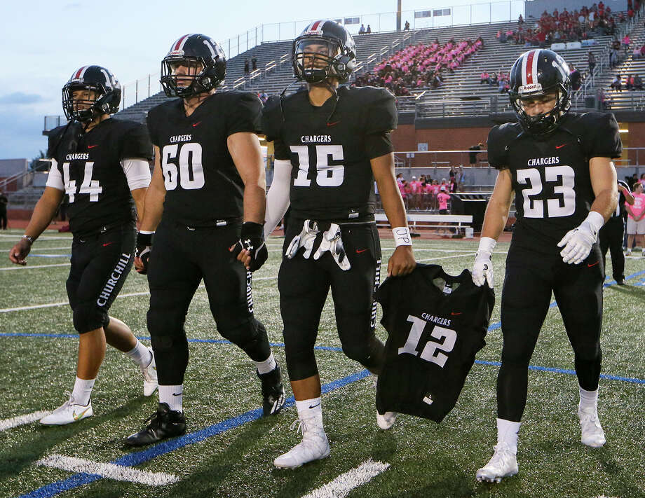 Churchill team captains Philip Mitschke (from left), Matthew Atkonis, Michael Sandoval and Thomas Sharrick carry the jersey of teammate Josh Pollard to the coin toss prior to the first half of their District 26-6A high school football game with Johnson at Heroes Stadium on Friday, Oct. 7, 2016.  MARVIN PFEIFFER/ mpfeiffer@express-news.net Photo: Marvin Pfeiffer/San Antonio Express-News