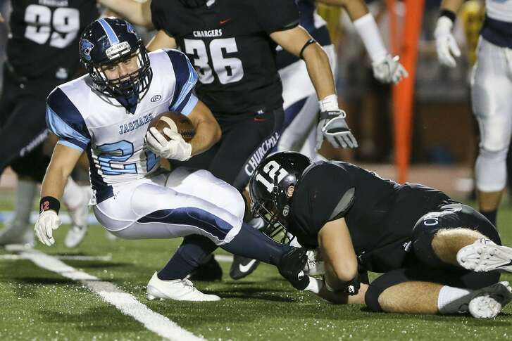 Johnson's Alex Apple (left) tries to spin away from Churchill's Cort Jaquess during the first half of a District 26-6A game at Heroes Stadium on Oct. 7, 2016.