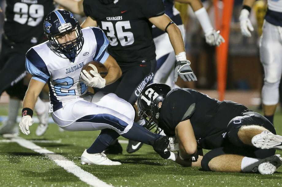 Johnson's Alex Apple (left) tries to spin away from Churchill's Cort Jaquess during the first half of a District 26-6A game at Heroes Stadium on Oct. 7, 2016. Photo: Marvin Pfeiffer /San Antonio Express-News / Express-News 2016