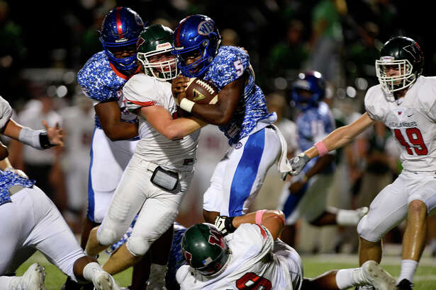 West Brook running  back James Jones gets tackled by The Woodlands defenders during the first quarter at the Thomas Center on Friday evening.  Photo taken Friday 10/7/16 Ryan Pelham/The Enterprise