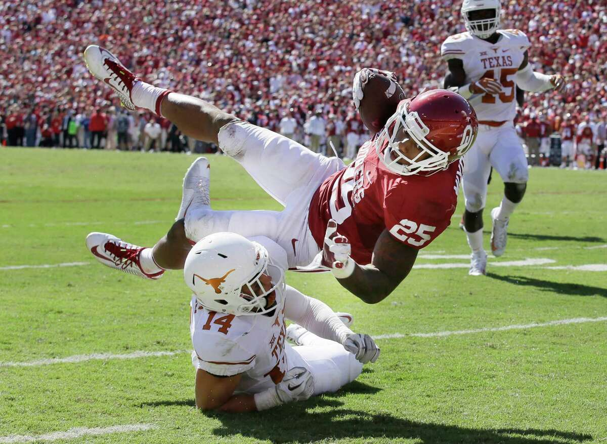Oklahoma running back Joe Mixon (25) is knocked off his feet by Texas safety Dylan Haines (14) during the first half of an NCAA college football game in Dallas Saturday, Oct. 8, 2016. (AP Photo/LM Otero)