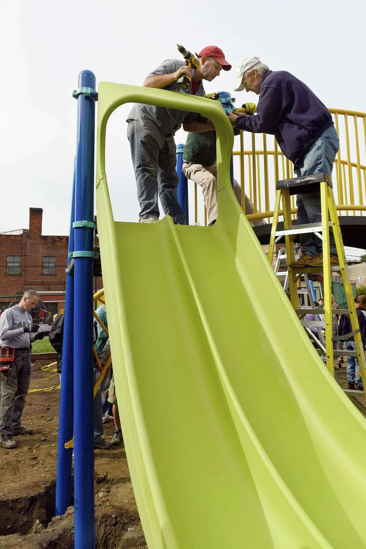 Paul Musser, left, and Rich Sinclair, right, of First Unitarian Universalist Society of Albany, attaches slide on the new playground on Saturday, Oct. 8, 2016, at Sheridan Preparatory Academy in Albany, N.Y. Other groups include Alpha Phi Alpha Fraternity Inc., UAlbany's Project U, Jack and Jill of America Greater Albany Chapter and SPA teachers, staff and families. Support for the project includes a $15,000 Let?'s Play Community Construction Grant from Dr. Pepper Snapple Group and national non-profit KaBOOM! SPA has raised $50,000 of its $60,000 goal for the project, and it has a Red Basket fundraising site to help raise the rest. To contribute, visit https://redbasket.org/1074 (Cindy Schultz / Times Union)