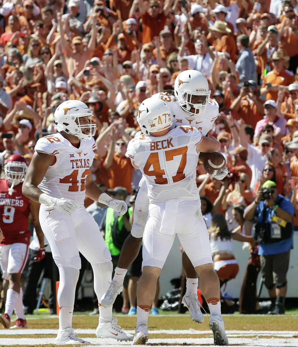 Texas running back D'Onta Foreman (33) celebrates running for a touchdown with teammates Andrew Beck (47) and Caleb Bluiett (42) during the first half of an NCAA college football game against Oklahoma in Dallas Saturday, Oct. 8, 2016. (AP Photo/LM Otero)