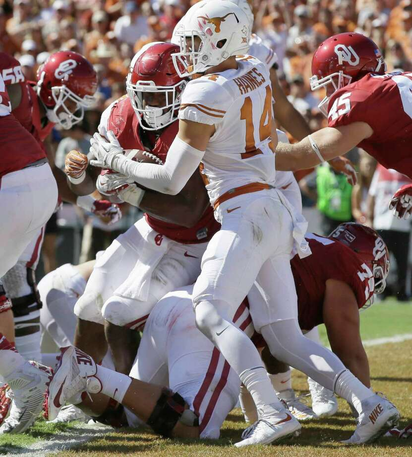 Oklahoma running back Samaje Perine (32) crosses the goal line scoring against Texas safety Dylan Haines (14) during the first half of an NCAA college football game in Dallas Saturday, Oct. 8, 2016. (AP Photo/LM Otero) Photo: LM Otero, Associated Press / Copyright 2016 The Associated Press. All rights reserved.