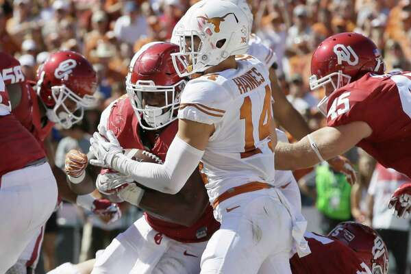 Oklahoma running back Samaje Perine (32) crosses the goal line scoring against Texas safety Dylan Haines (14) during the first half of an NCAA college football game in Dallas Saturday, Oct. 8, 2016. (AP Photo/LM Otero)