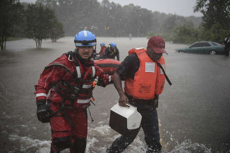 A rescue team member leads Derrick Williams (right) out of the water at a freeway ramp in Fayetteville, N.C. Hurricane Matthew was blamed for at least 10 deaths in the United States. Photo: Andrew Craft, Associated Press