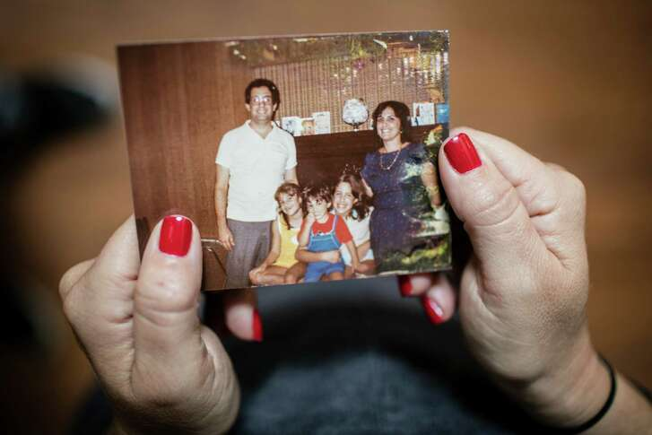 Needleman displays a family photo from her childhood at her home in Pikesville, Md.
