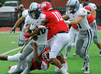 Staples running back Elliott Poulley is tackled by an NFA defender Saturday. Staples lost 33-14.
