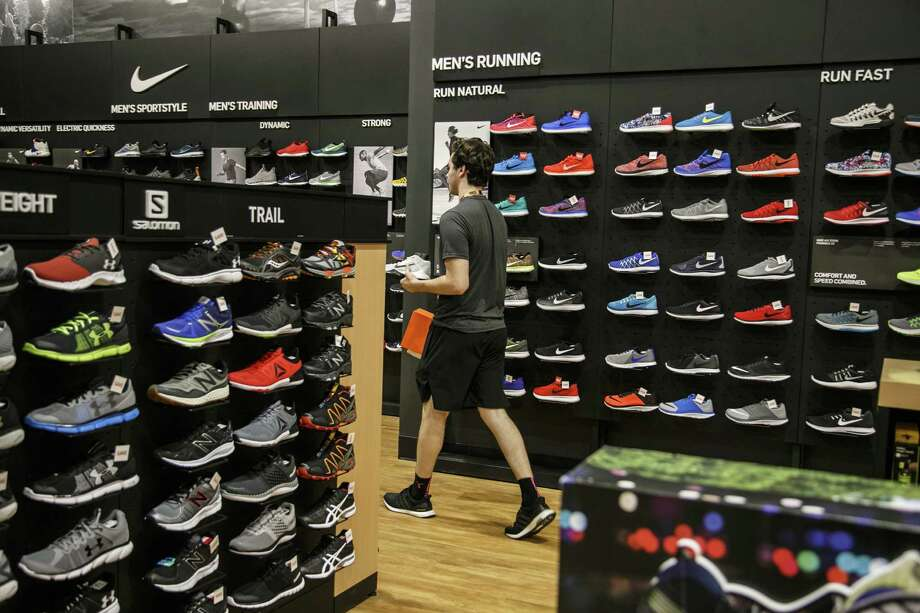 An employee carries Nike Inc. sneakers for a customer at a Dick's Sporting Goods Inc. store in Sterling Heights, Michigan. The company is preparing to open a store in Friendswood near Baybrook Mall. Photo: Sean Proctor / © 2016 Bloomberg Finance LP