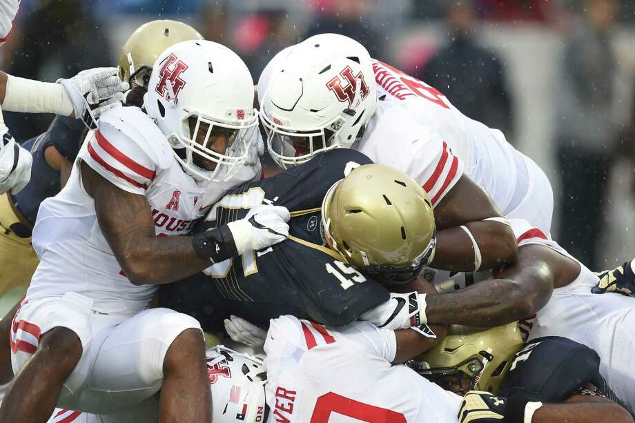 ANNAPOLIS, MD - OCTOBER 08:  Will Worth #15 of the Navy Midshipmen is tackled by D'Juan Hines, Nick Thurman #91, and Ed Oliver #10 of the Houston Cougars during  the first period of a football game at Navy-Marines Memorial Stadium on October 8, 2016 in Annapolis, Maryland. Photo: Mitchell Layton, Getty Images / 2016 Getty Images