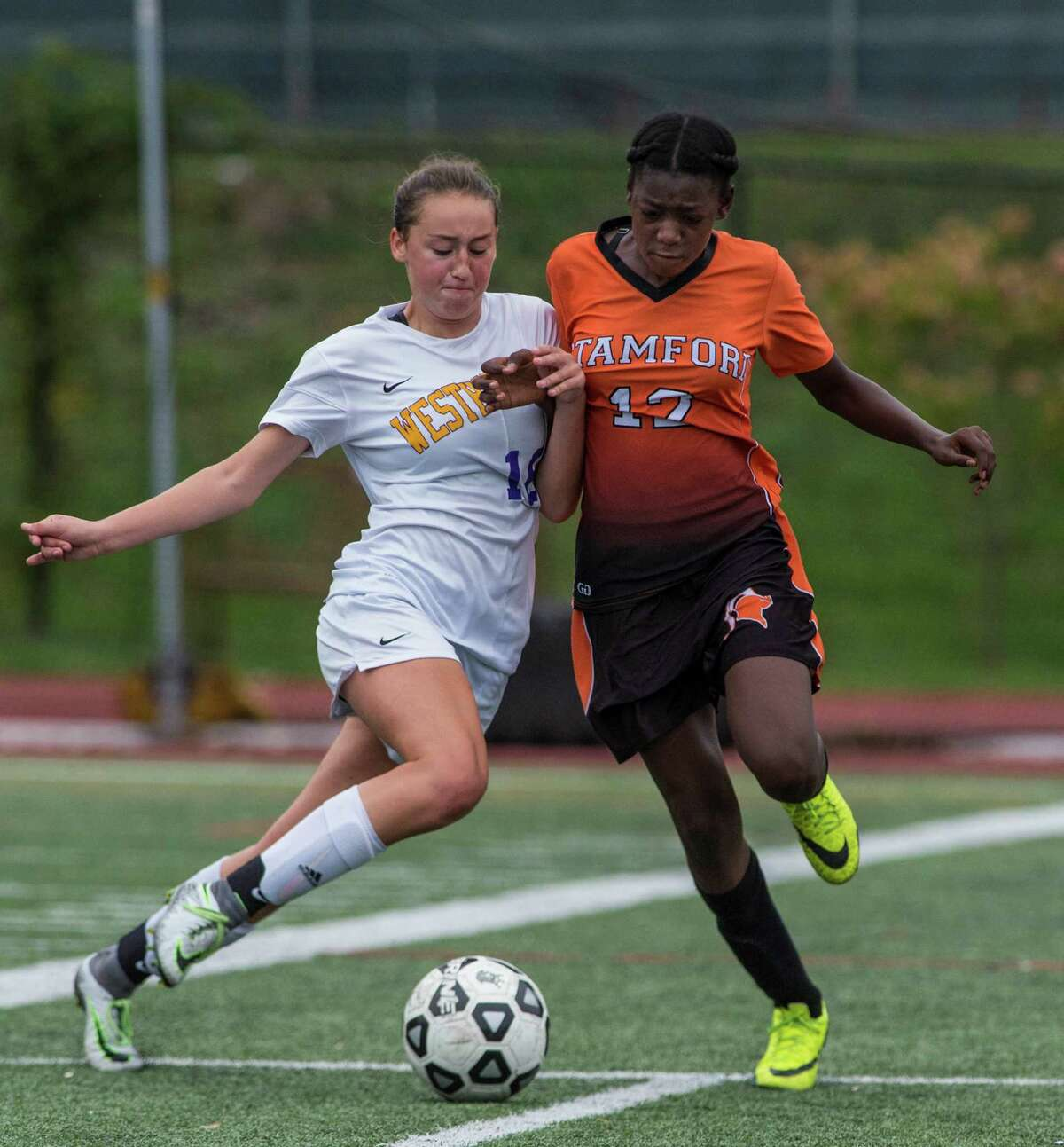 Westhill's Lilly Gubernick, left, and Stamford's Chanille Assevero battle for the ball during a girls soccer game played at Westhill High School in Stamford on Saturday. Westhill won the city championship, 3-0.