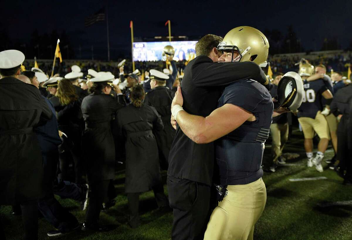 Navy quarterback Will Worth, right, gets a hug from a midshipmen after an NCAA football game against Houston, Saturday, Oct. 8, 2016, in Annapolis, Md. Navy won 46-40. (AP Photo/Nick Wass)