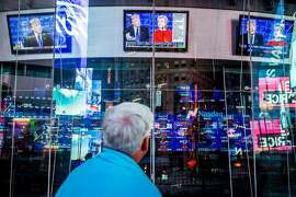 A man follows the debate between Hillary Clinton and Donald Trump, at Times Square in New York, Sept. 26, 2016. Monday's face-off is among the most highly anticipated presidential debates in American history. (George Etheredge/The New York Times)