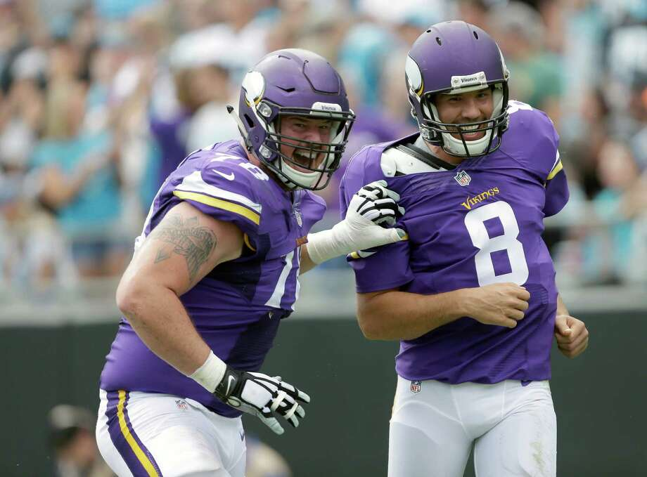 Vikings offensive lineman Jeremiah Sirles, left, celebrates a touchdown with quarterback Sam Bradford. The Vikings and their 4-0 record have been one of the NFL's surprises this season. Photo: Bob Leverone, FRE / FR170480 AP