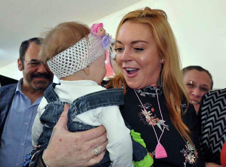 U.S. actress Lindsay Lohan holds a Syrian refugee child as she visits a Turkish government-run Syrian refugee camp in Nizip near Turkey's border with Syria, Saturday, Oct. 8, 2016. The Anadolu Agency said Saturday the U.S. actress toured the social facilities and preschool in Nizip before giving refugee children there presents. (AP Photo) ORG XMIT: ANK803 / Copyright 2016 The Associated Press. All rights reserved.