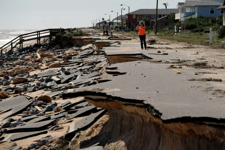 Onlookers walk along a section of highway A1A that was washed out by Hurricane Matthew on Saturday in Flagler Beach, Fla. Matthew washed out roads and knocked out power for more than 1 million people.  Photo: Eric Gay, STF / Copyright 2016 The Associated Press. All rights reserved.