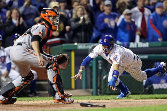San Francisco Giants' Buster Posey awaits the throw as Chicago Cubs' Javier Baez scores on Kyle Hendricks' 2-run single in 2nd inning during Game 2 of the National League Division Series at Wrigley Field in Chicago. IL, on Saturday, October 8, 2016.