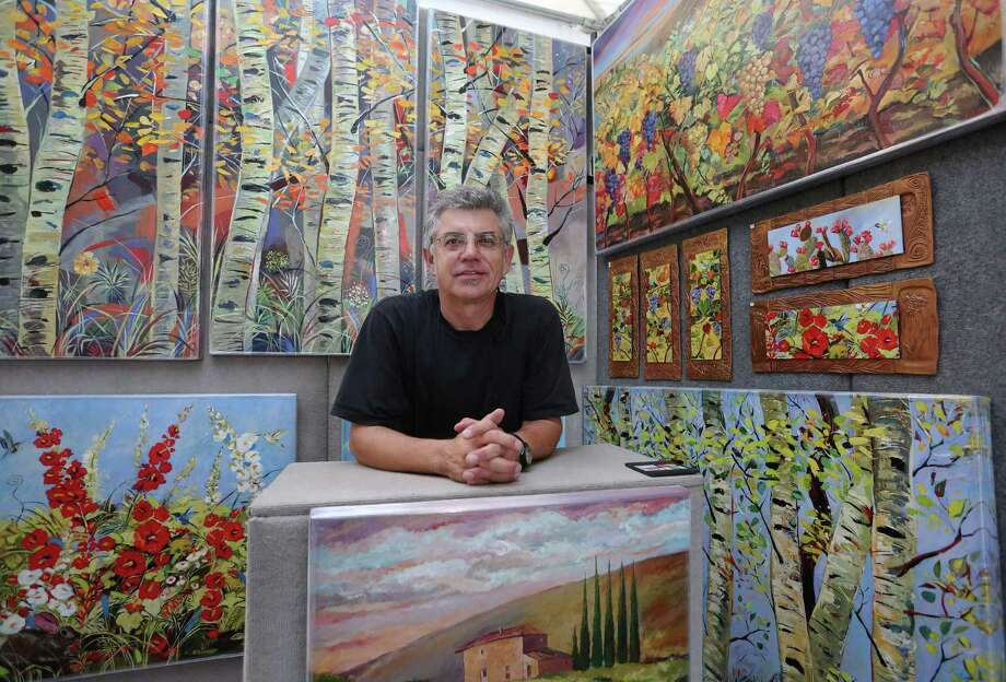 """Painter Miro Kenarov poses for a photo with his """"Canvas on Clay"""" collections at the annual Bayou City Art Festival on Saturday.  Photo: Yi-Chin Lee, Staff / © 2016  Houston Chronicle"""