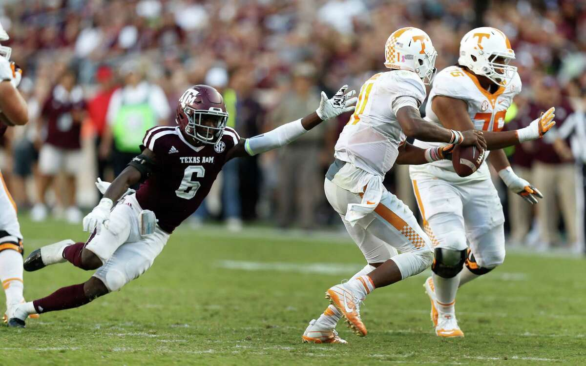 Texas A&M Aggies defensive back Donovan Wilson (6) reaches for Tennessee Volunteers quarterback Joshua Dobbs (11) during the fourth quarter of a college football game at Kyle Field, Saturday, Oct. 8, 2016 in College Station.